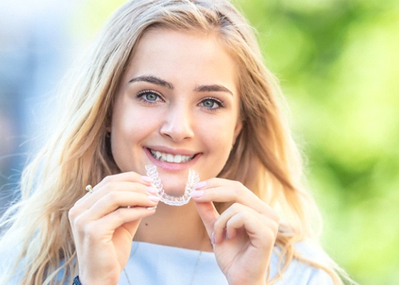 A young woman holding an Invisalign aligner and preparing to place it in her mouth