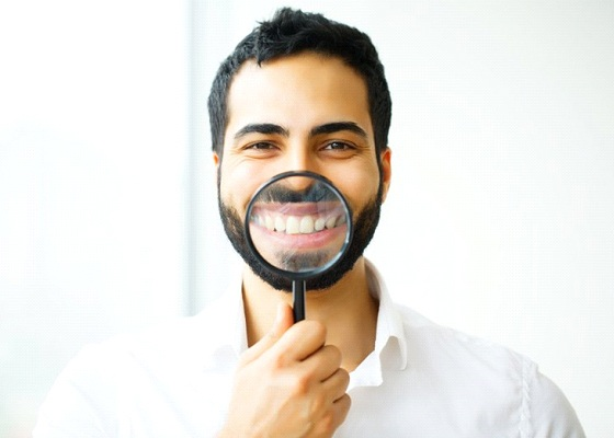 man holding magnifying glass to his smile after teeth whitening in Annapolis
