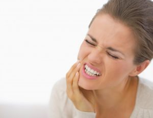 woman holding jaw from tooth pain
