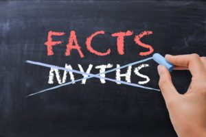"person crossing out ""myths"" on a chalkboard and writing ""facts"" in its place"