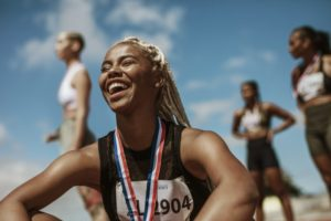 track runner smiling and sitting down with a metal around their neck