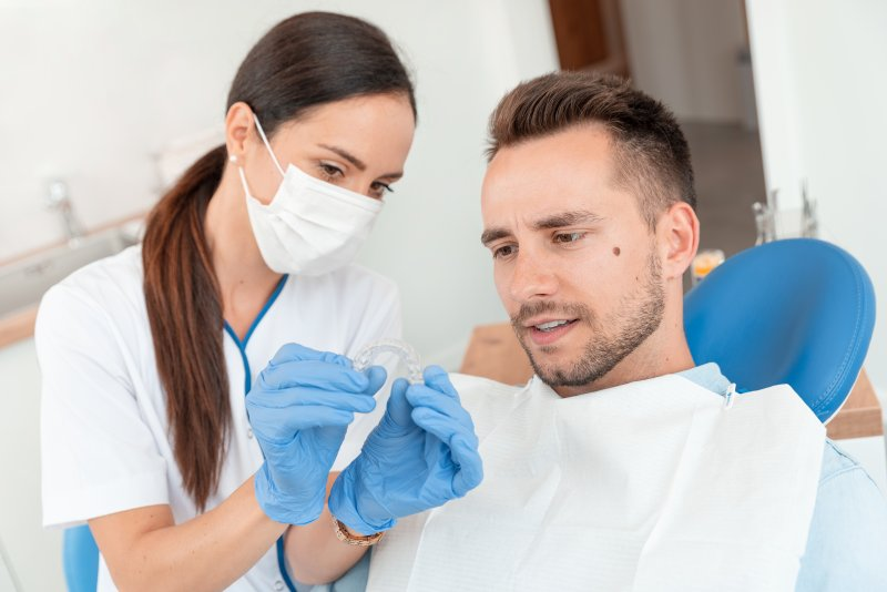 Dentist showing patient Invisalign trays