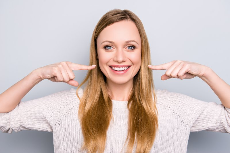 Woman pointing to her straight, white smile