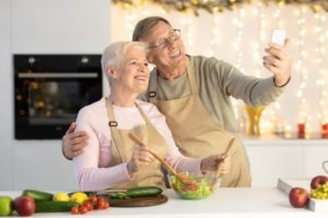 Man and woman in a kitchen smiling and taking a selfie