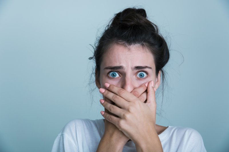 woman in shock with hand over mouth